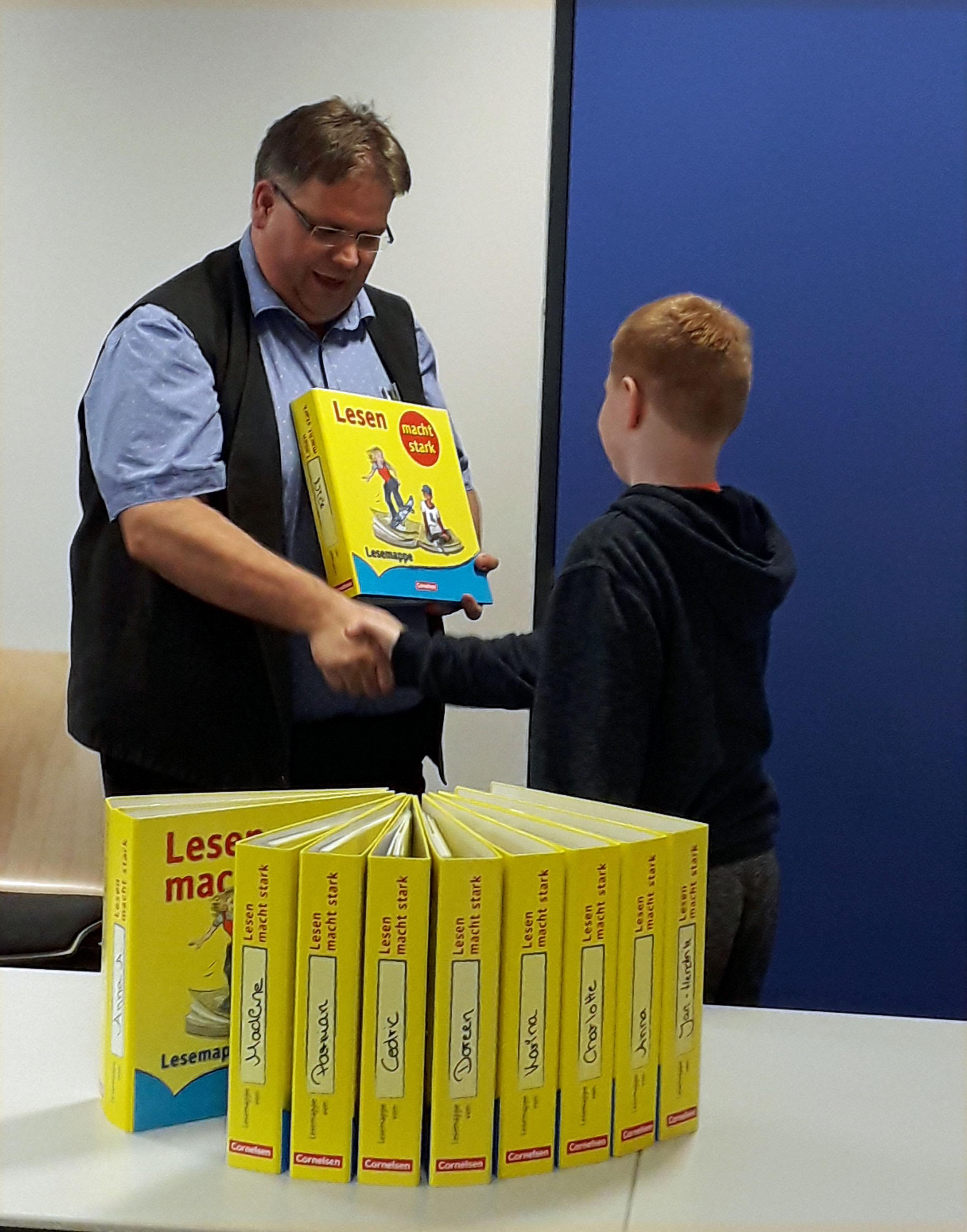 Rektor Sander übergibt einen Leseordner